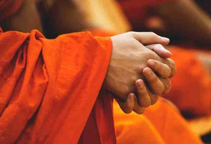 Clasped hands of Buddhist monk in orange robe.