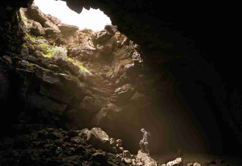 Hiker heading toward daylight light from deep inside cave