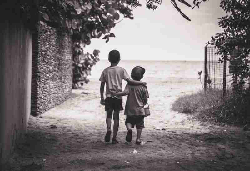Young boys walking arm-in-arm toward the beauty of the sea