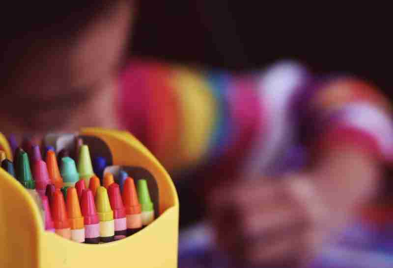 Child showing kindness by making a drawing with crayons